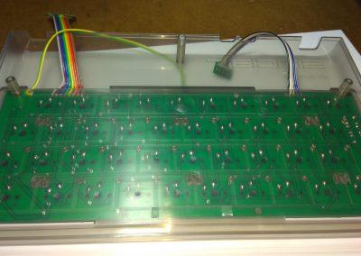Vista inferior de la tapa con el teclado fijado y los cables pasados.